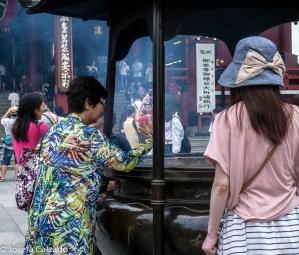 Detalle turista llevándose el humo hacia la cabeza